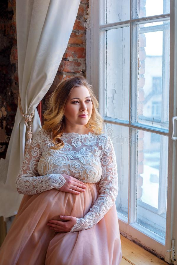 等待在窗口的孕妇,在一件美丽的礼服,母性 免版税图库摄影