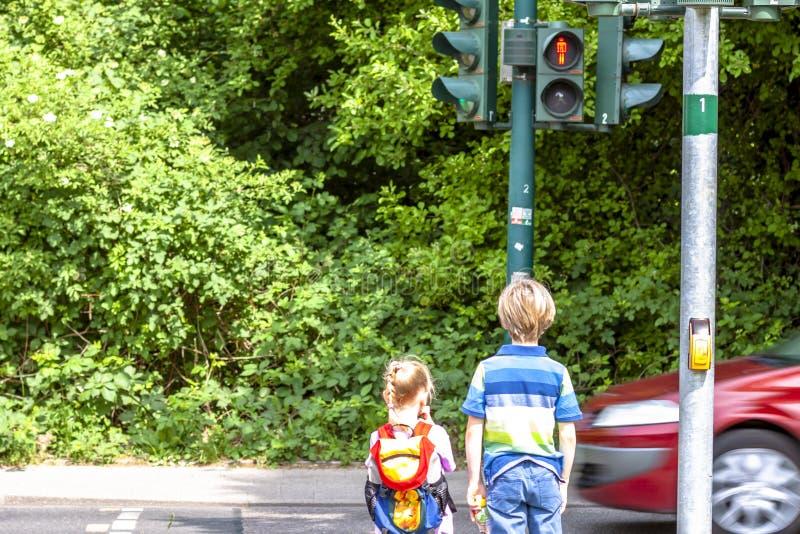等待在红色红绿灯的男孩和女孩 图库摄影