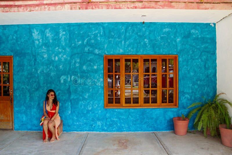 等待在蓝色墙壁前面的女孩在Sayulita 免版税库存图片