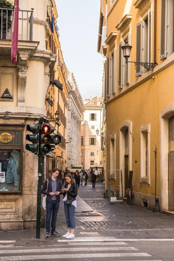 等待在行人穿越道的夫妇在中心在罗马 免版税库存图片