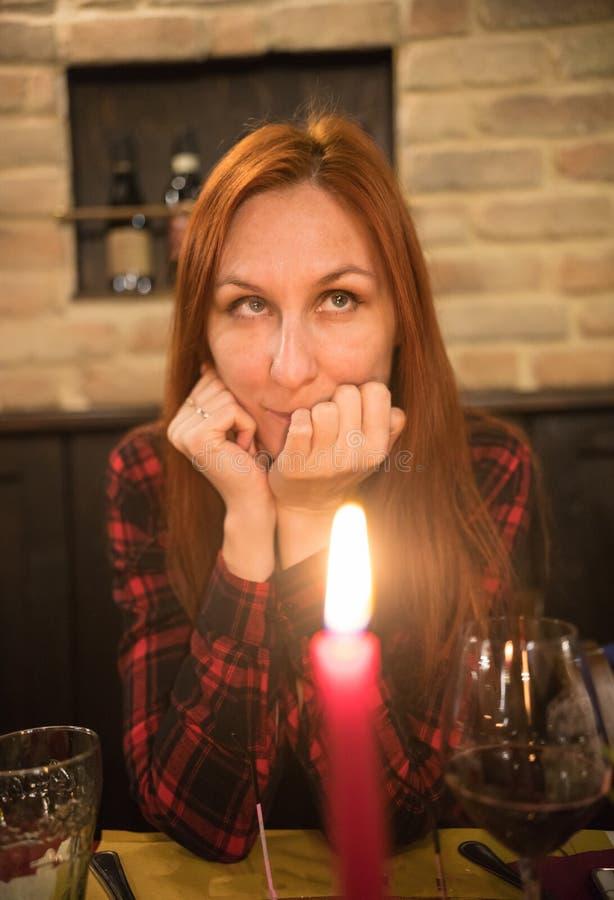 等待在reustarant的愉快的俏丽的redhair妇女 在前景的一个被点燃的蜡烛 库存照片