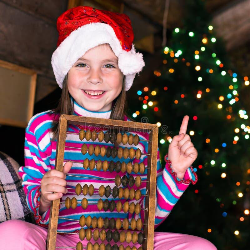 等待奇迹的圣诞节帽子的愉快的儿童女孩 免版税库存照片
