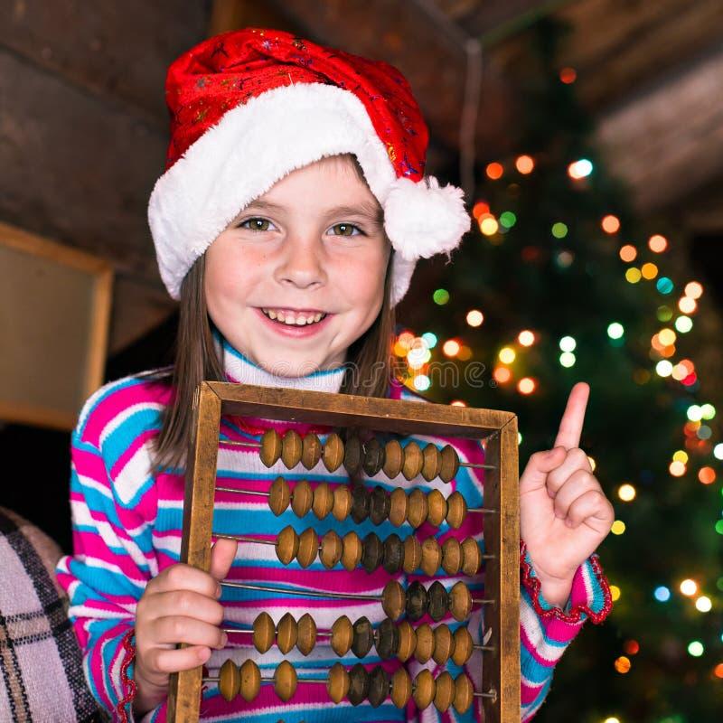 等待奇迹的圣诞节帽子的愉快的儿童女孩 免版税库存图片