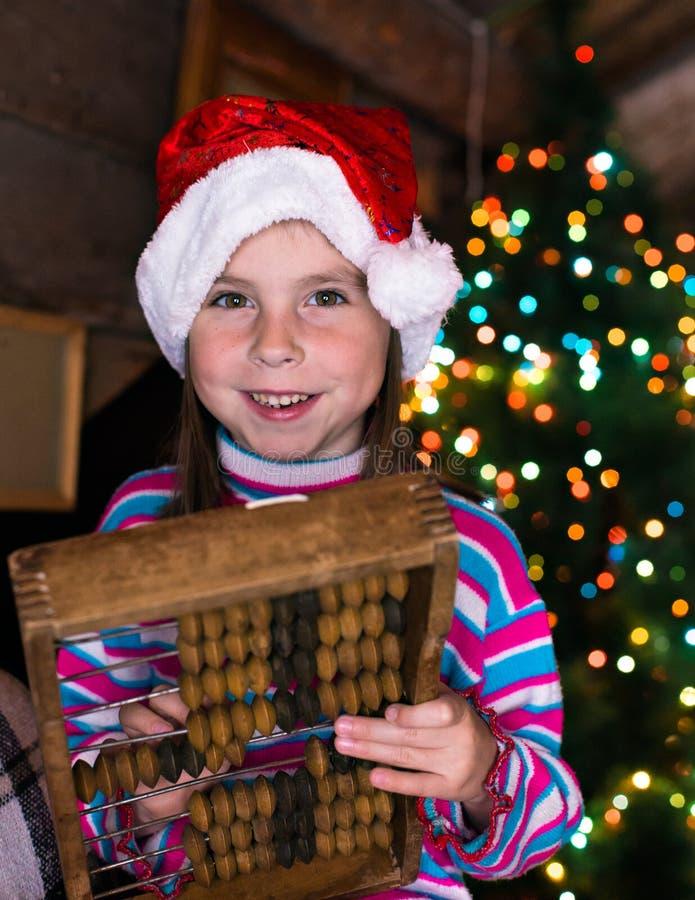等待奇迹的圣诞节帽子的愉快的儿童女孩 库存图片