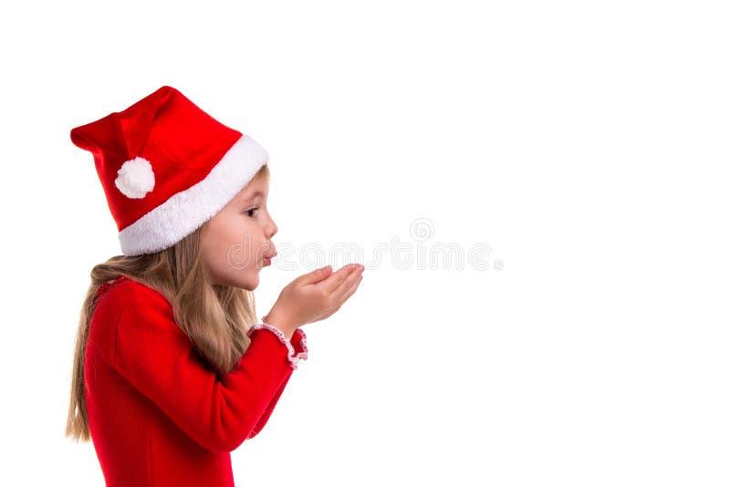 等待奇迹 握手和吹在他们上的外形观点的圣诞节女孩在白色被隔绝 库存照片