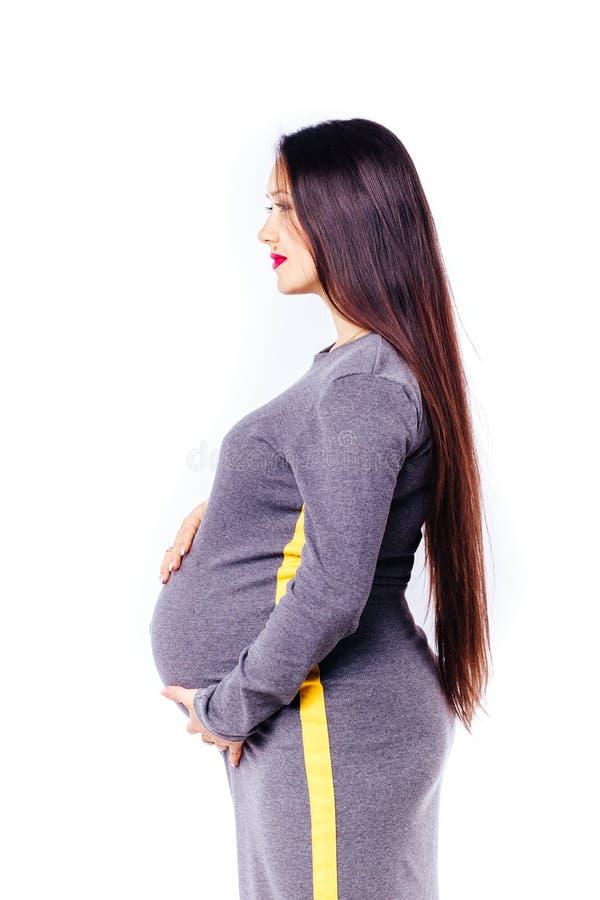 等待她的婴孩的怀孕的年轻女人 免版税库存照片