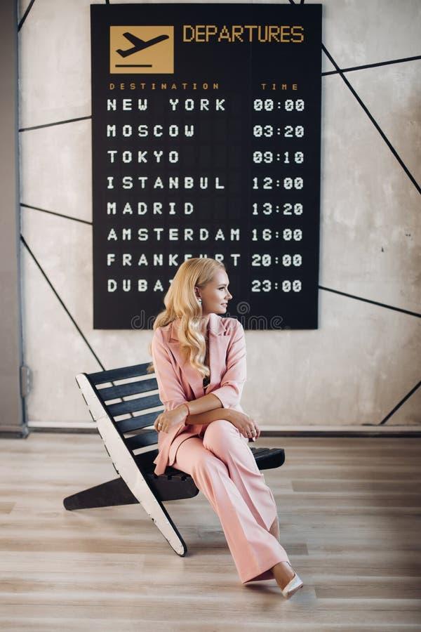 等待她的飞行的桃红色衣服的时兴的夫人在机场 免版税库存图片