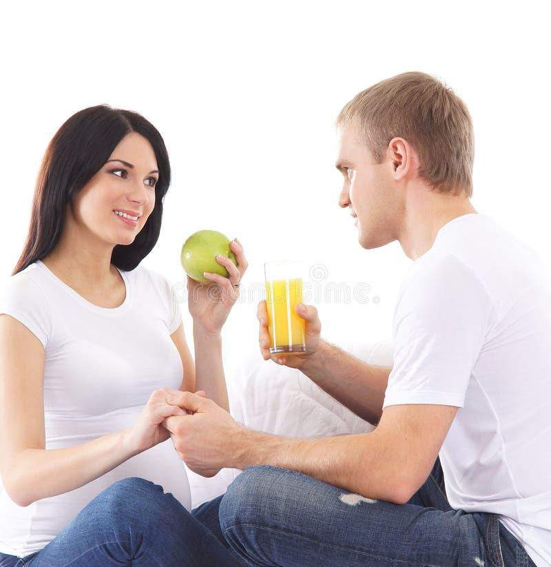等待婴孩和吃健康食物的一对愉快的夫妇 库存图片