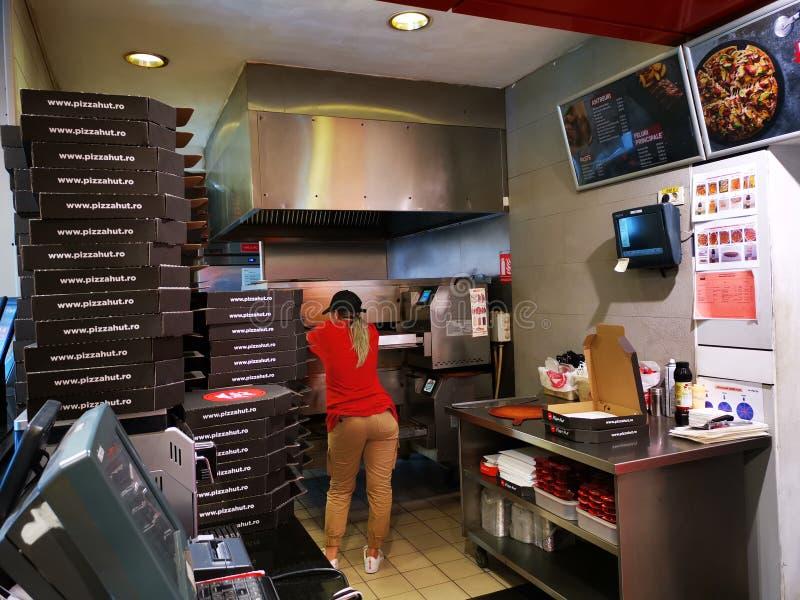 等待对比萨的妇女在烤箱外面在室内到达必胜客交付 库存照片
