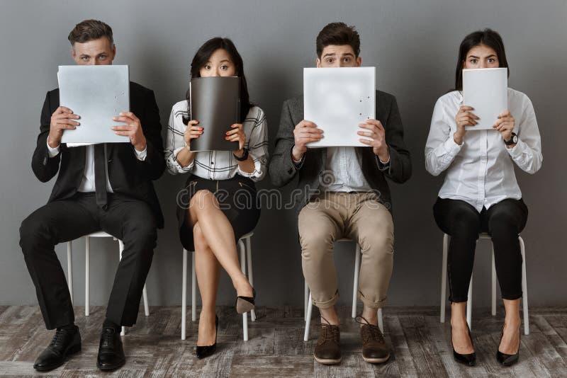 等待工作面试的多文化商人和笔记本被遮暗的看法有文件夹的 库存照片