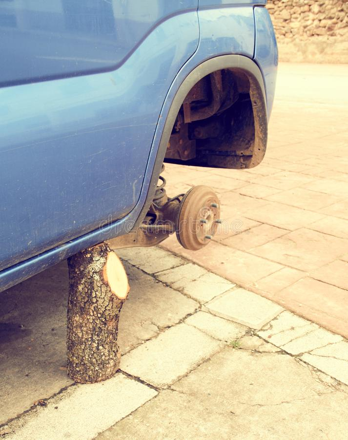 等待方向盘的一辆老汽车 一辆汽车没有轮胎和支持由是一个木树桩的起重器 免版税库存图片