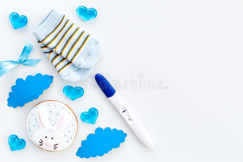 等待有正面妊娠试验、袜子和心脏白色背景顶视图大模型的一个婴孩 免版税库存照片