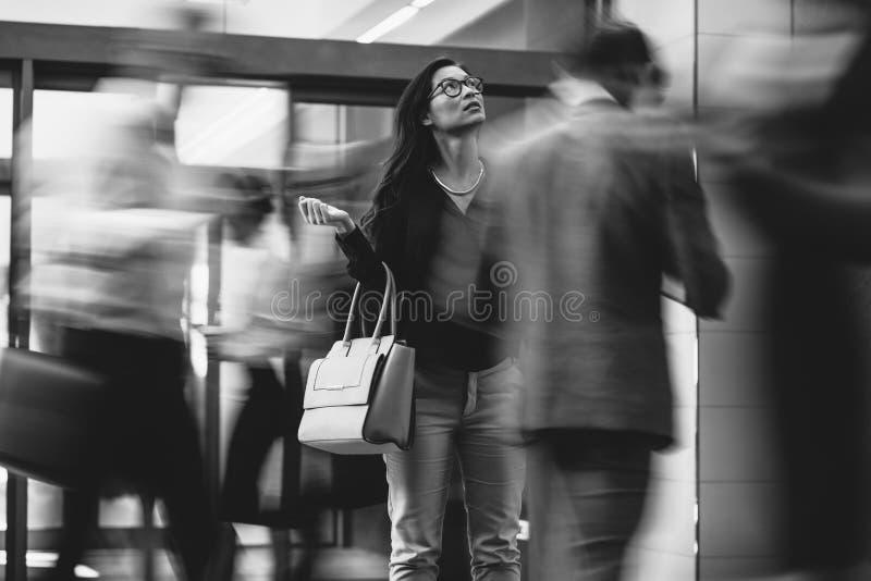 等待某人一个繁忙的大厅的女实业家 免版税库存照片
