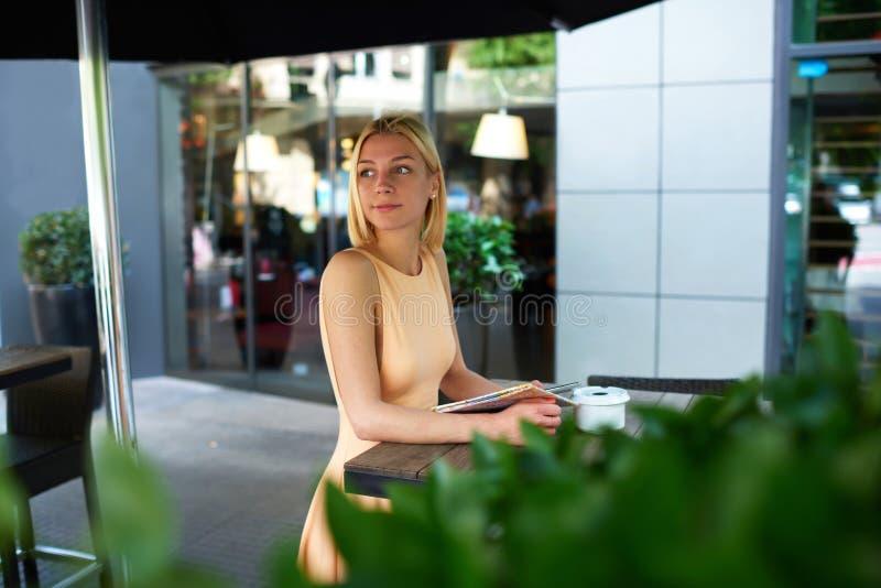 等待某人的迷人的女性行家在与绿色植物的边路咖啡馆 免版税图库摄影