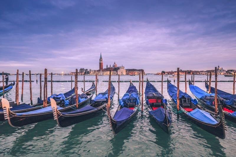 等待游人的长平底船在日落以后在威尼斯 免版税图库摄影