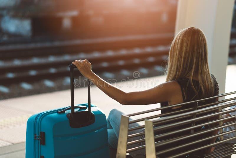 等待火车和拿着她的行李的妇女乘客 库存图片