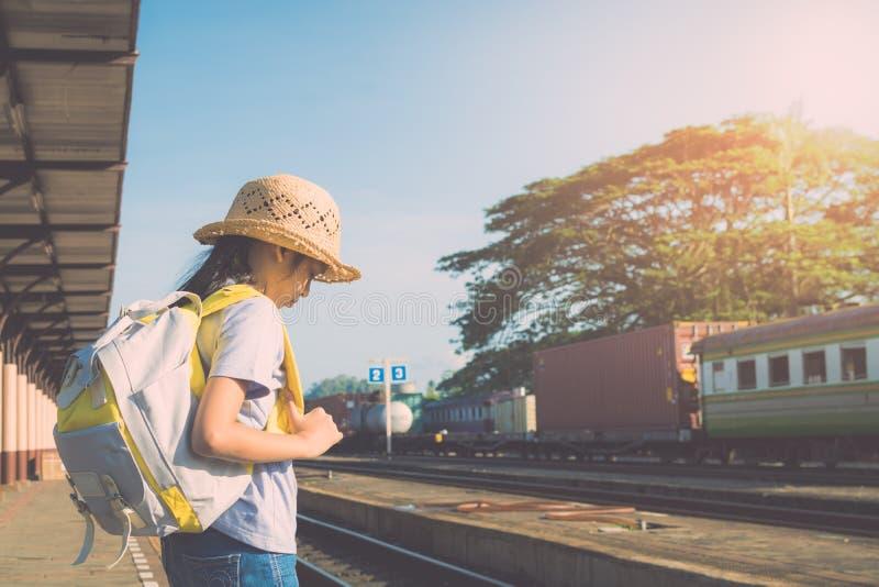 等待火车的女孩在火车站 免版税库存照片