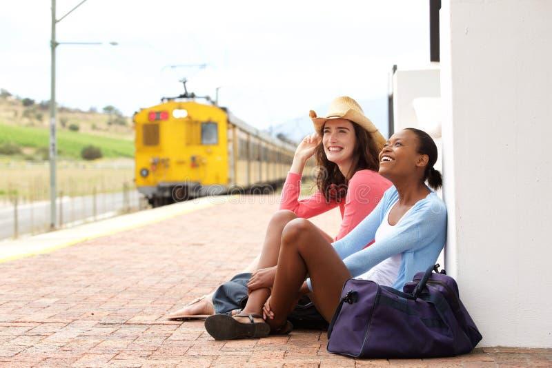 等待火车的女性朋友在火车站 免版税库存照片