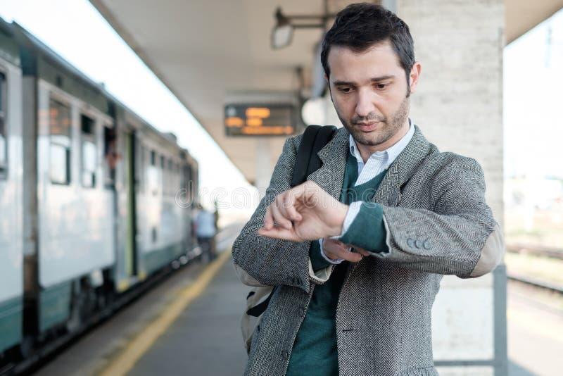 等待火车的常设人 免版税库存图片