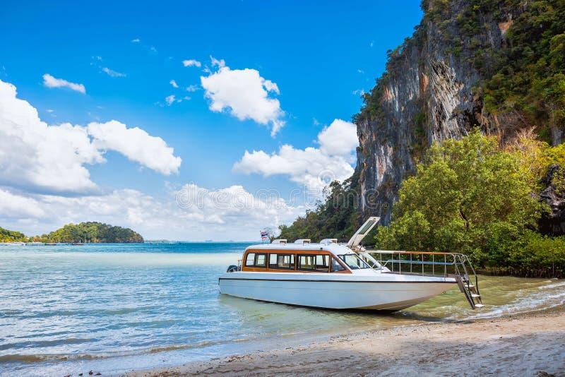 等待的乘客 在一个热带海岛的岸的雪白优质快艇 停泊在一个沙滩、热带和岩石 免版税图库摄影