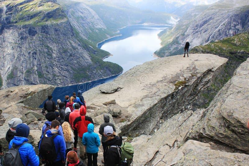 等待的人民在trolltunga排行做摄影拖钓` s舌头岩石,挪威 免版税图库摄影