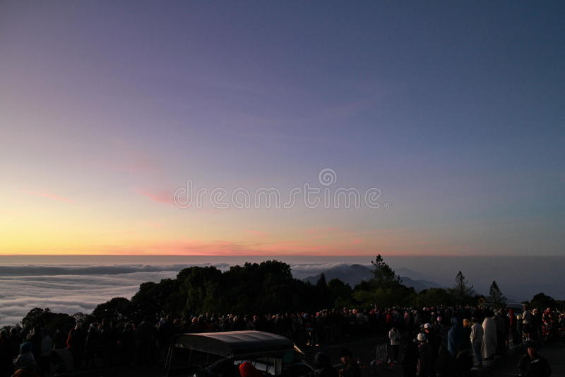 等待的人们看太阳上升在山顶部 免版税库存照片