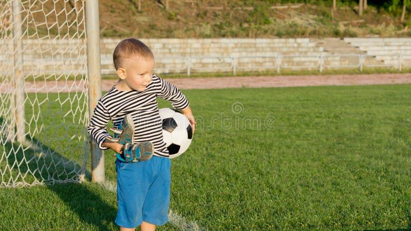 等待的小男孩踢足球 免版税库存照片