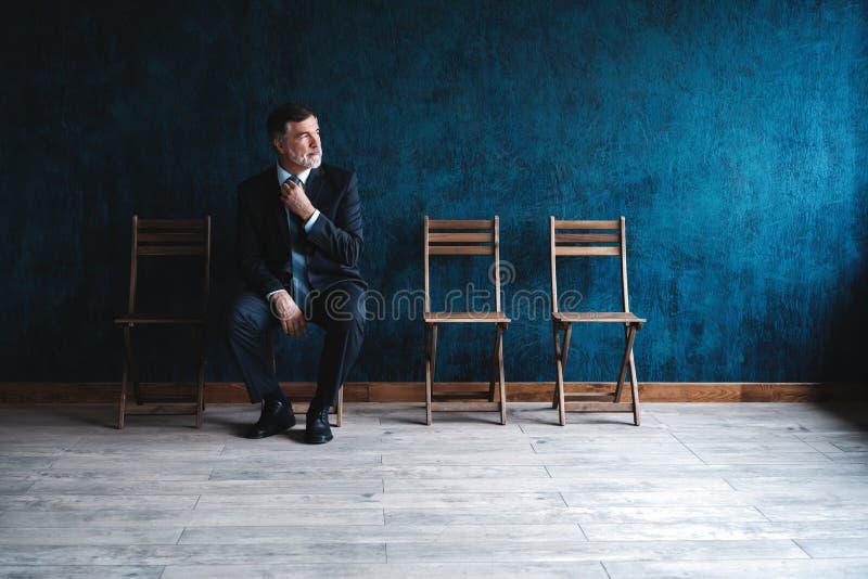 等待的采访 确信的成熟商人坐椅子反对深蓝背景 免版税库存照片