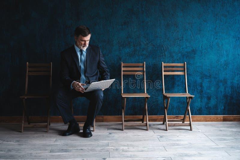 等待的采访 确信的成熟商人坐椅子反对深蓝背景 免版税图库摄影