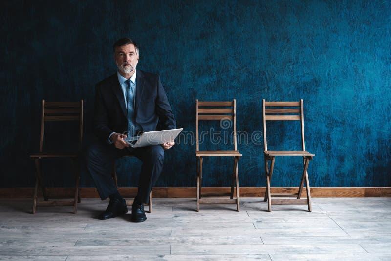等待的采访 确信的成熟商人坐椅子反对深蓝背景 库存图片