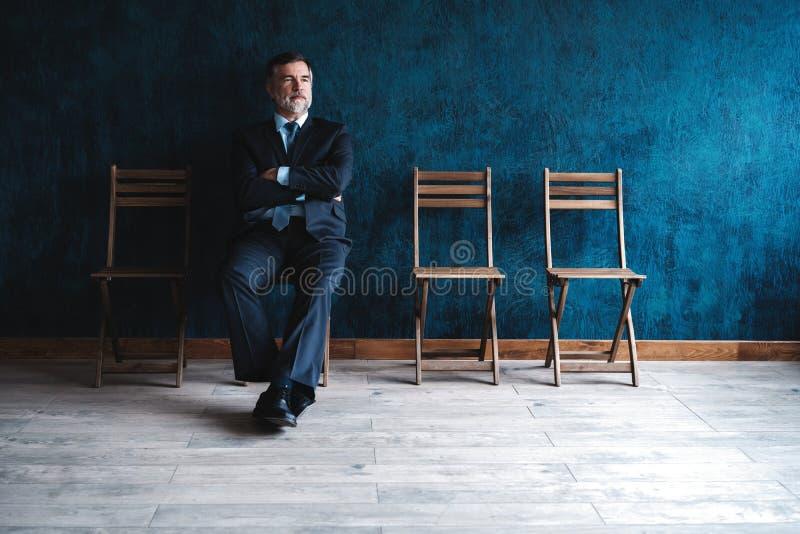 等待的采访 确信的成熟商人坐椅子反对深蓝背景 免版税库存图片