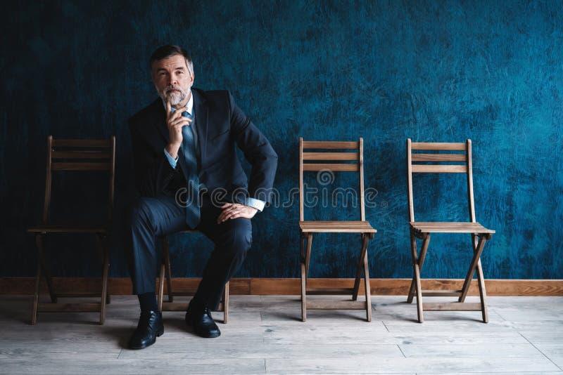 等待的采访 确信的成熟商人坐椅子反对深蓝背景 图库摄影