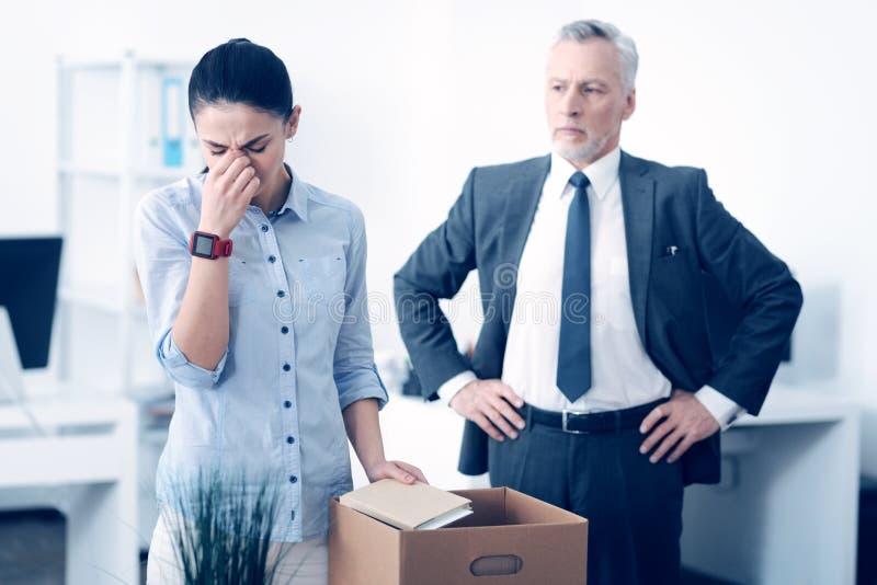 等待被解雇的雇员的严肃的院长离开他的办公室 图库摄影