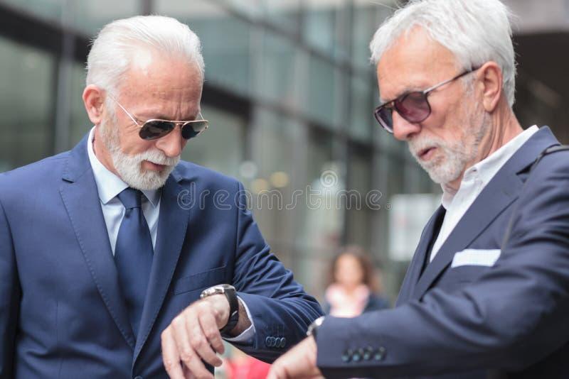等待重要会议的两个严肃的灰发的资深商人 免版税库存照片