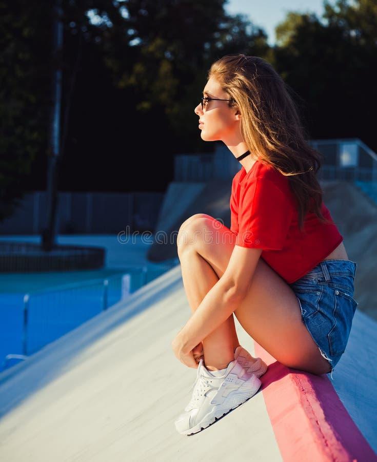 等待 告别 女孩坐温暖的太阳光芒的舷梯冰鞋公园  室外,夏天 免版税图库摄影