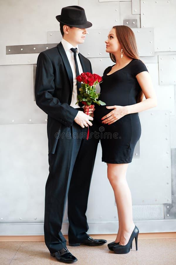等待婴孩的时髦的典雅的年轻夫妇 库存图片