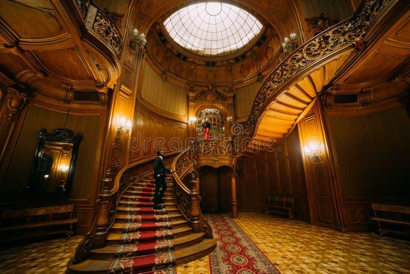 等待他的葡萄酒台阶的英俊的非洲人女朋友 豪华剧院内部背景 图库摄影