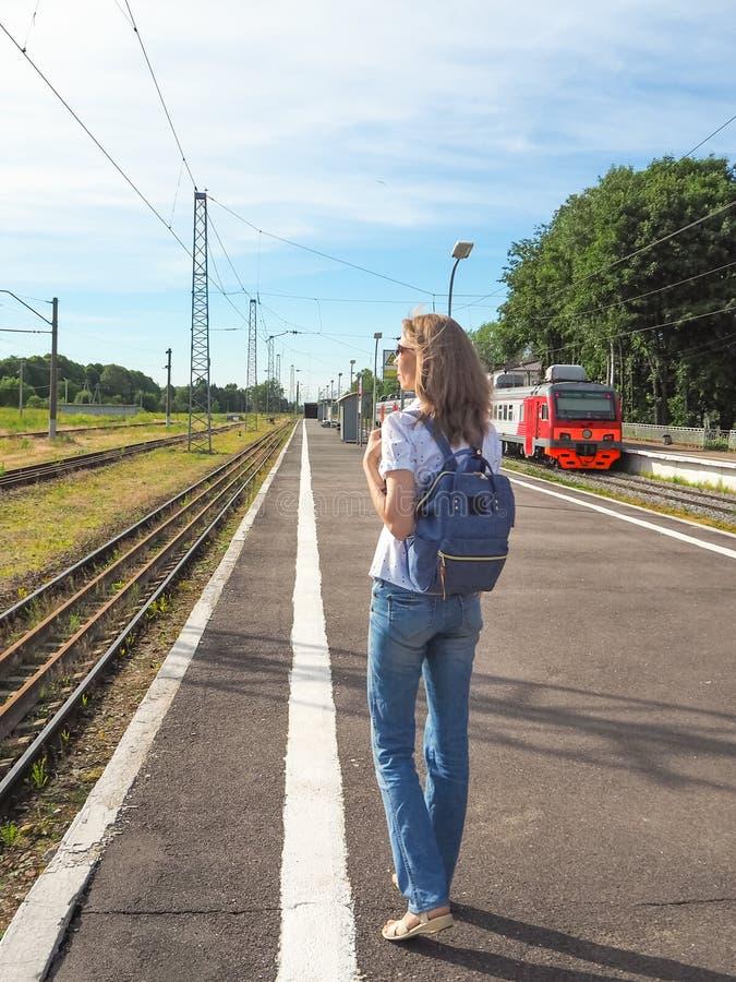 等火车的俏丽的妇女在火车站旅行在夏天 汽车城市概念都伯林映射小的旅行 免版税图库摄影