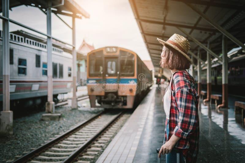 等火车的俏丽的妇女在火车站旅行在su 免版税库存照片