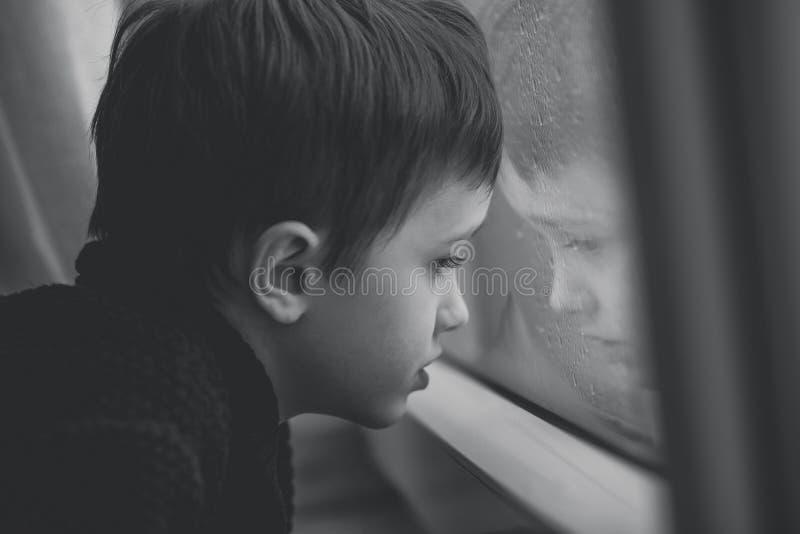 等由窗口的小男孩下雨的中止-黑白 库存照片