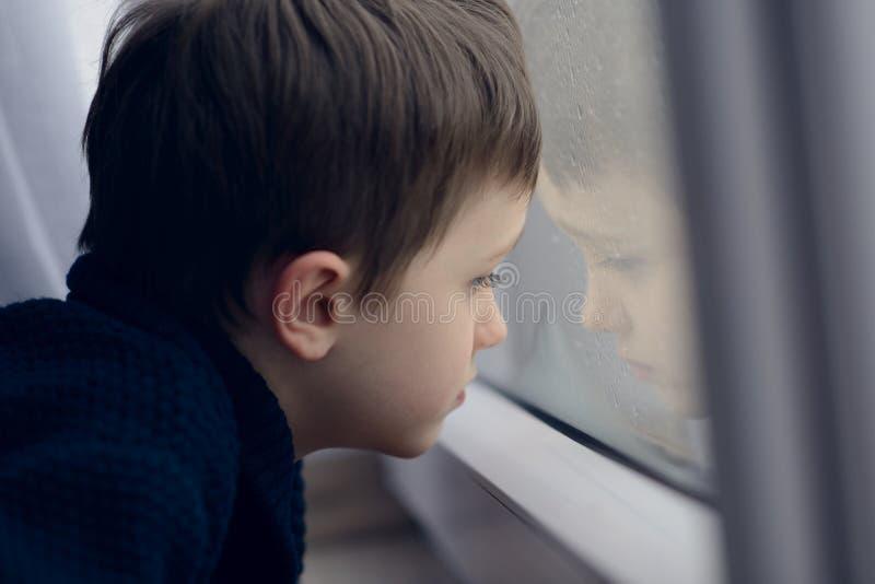等由窗口的小男孩中止下雨 免版税库存图片