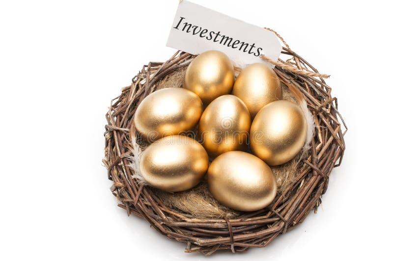 筑巢用与标记的金黄鸡蛋和投资的词在白色背景的 成功的退休的概念 免版税图库摄影