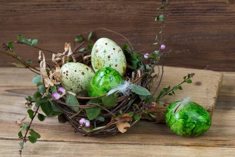 筑巢用在木背景的色的复活节彩蛋 免版税库存图片