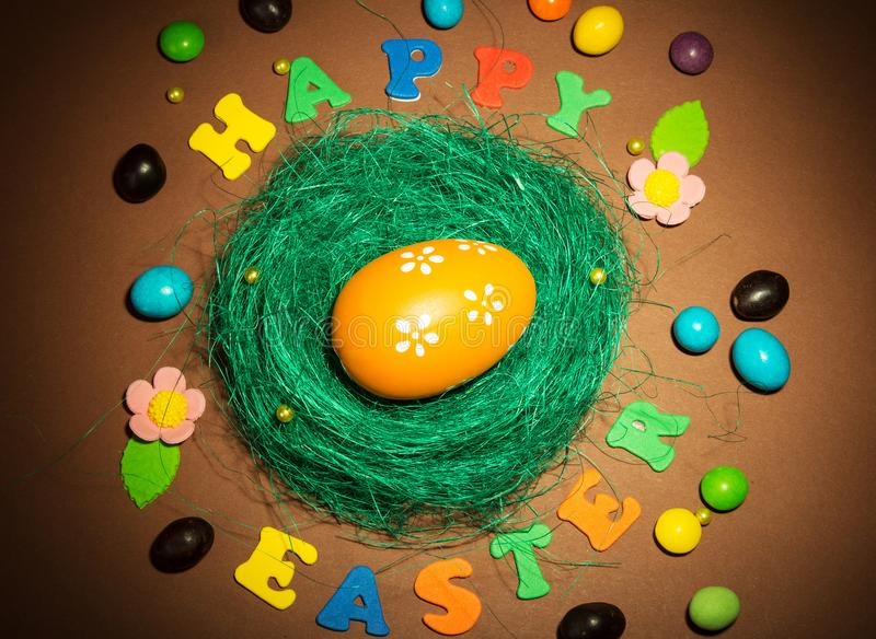 筑巢用复活节彩蛋、愉快的复活节题字、糖果和flowe 免版税库存图片