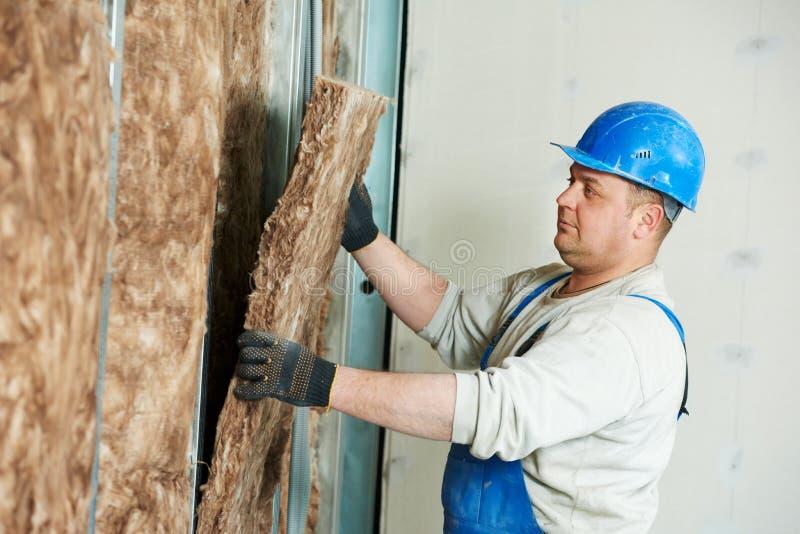 建筑工人在绝缘材料工作 库存照片