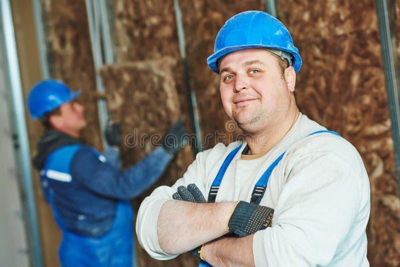 建筑工人在绝缘材料工作 免版税库存图片