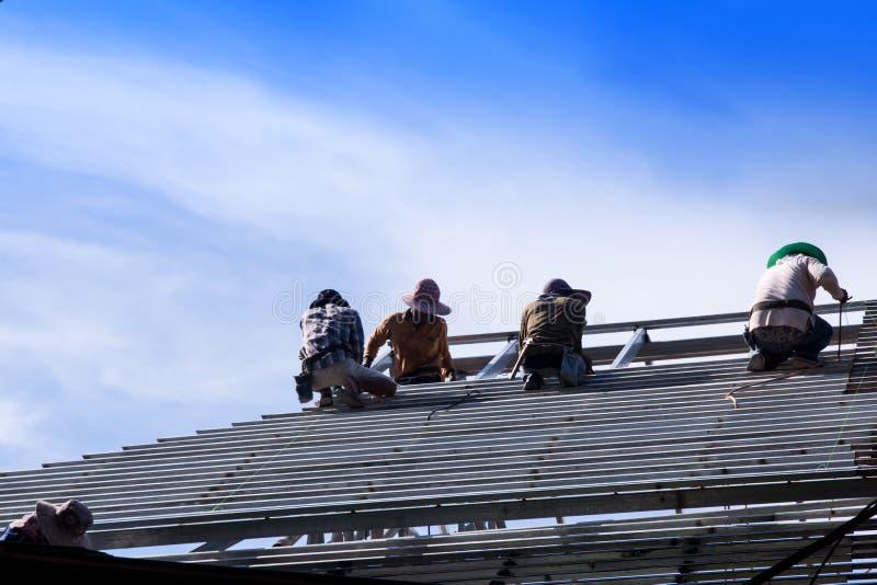 建筑工人安装钢屋顶 库存图片