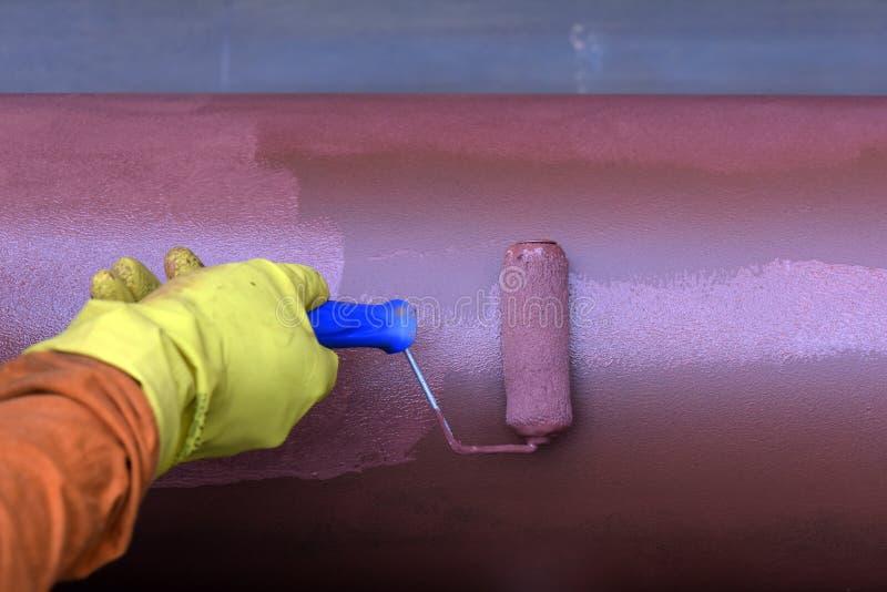 建筑工人防止的绘画输送管道受到铁锈 库存图片