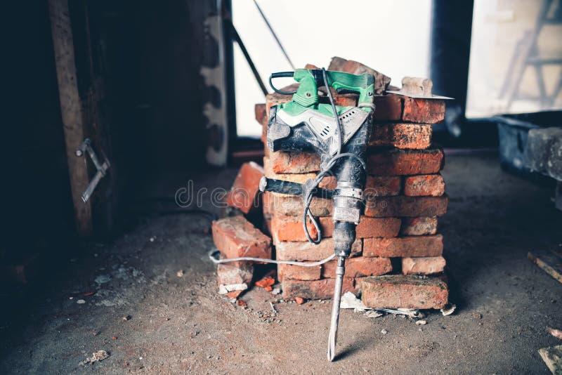 建筑工具、工业手提凿岩机有爆破残骸的和砖 免版税图库摄影