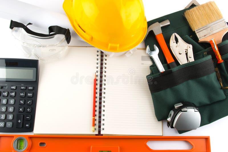 建筑工具和空白的笔记薄在白色背景 库存照片